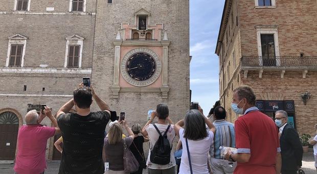 Turisti in piazza della Libertà sotto la Torre dell'orologio