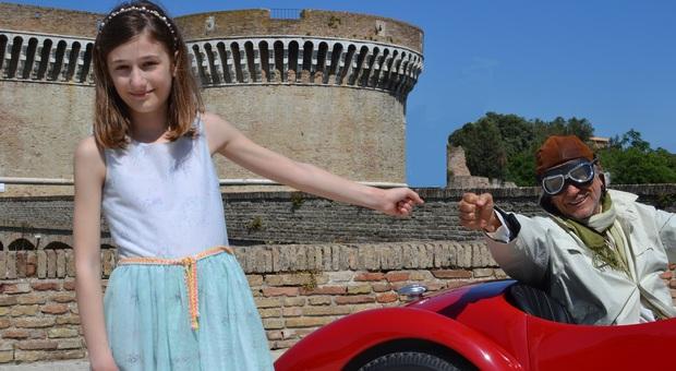 Elena Schiavoni nei panni della bambina, protagonista del ritrovamento delle bobine con le corse, mentre saluta il passaggio di un auto storica davanti alla Rocca roveresca di Senigallia